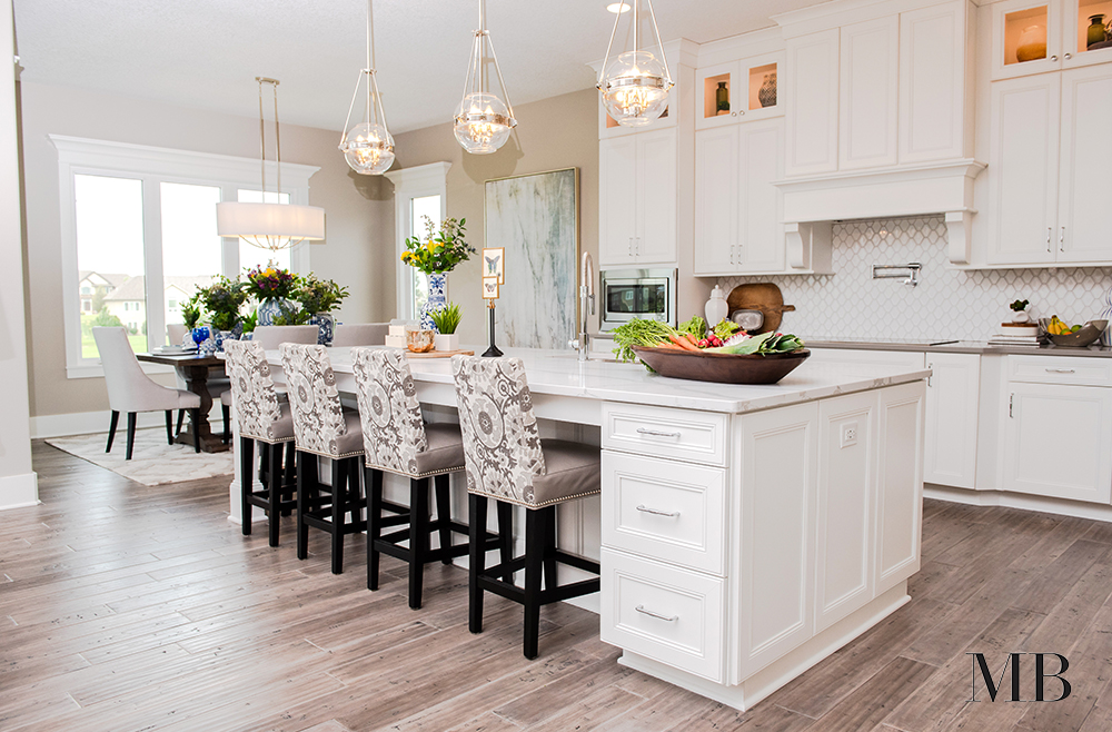 A luxe kitchen can be hard to pull off when it's part of a great room. Intricate detailing in the cabinetry, hardware and lighting, the extras make the space feel set apart while the neutral color palette and efficient footprint keep it from being distracting from the other spaces.