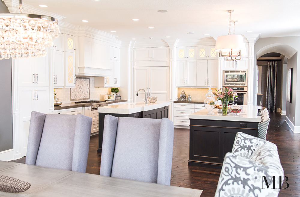 One island just isn't enough sometimes. For this kitchen, two islands give plenty of prep and entertaining space. The depth of island color anchors the white, custom cabinetry. Glamorous finishes and materials make for a stately, refined space.