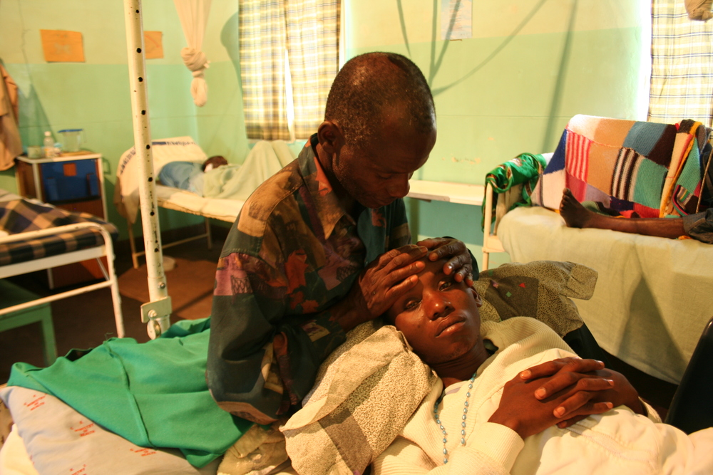 AGONY: A father's hands comfort his son, who is suffering an attack of cerebral malaria
