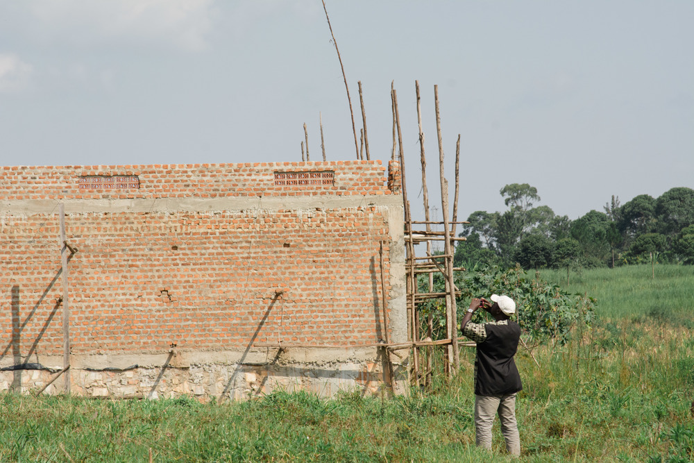 Rev. Raymond Kaija photographs the construction site of the seminary.