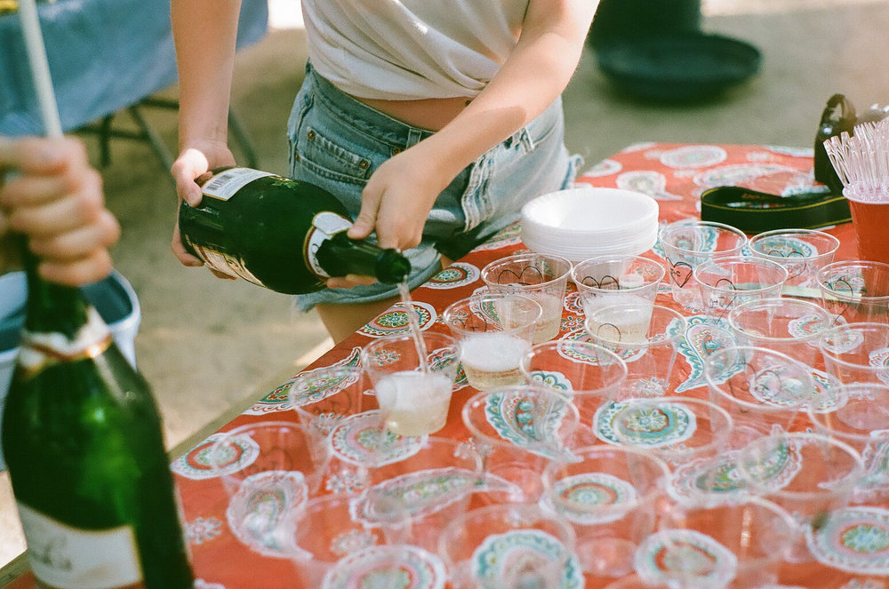 Gretta pouring champagne into hand-embellished plastic cups