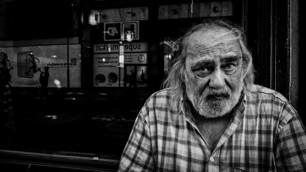 """""""Vroeger kon ik direct de bus nemen. Nu moet ik te voet gaan en hier op het terras wachten. Tot de bus komt...."""", zegt Daniel. Straatfotografie in Brussel - portret van Daniel"""