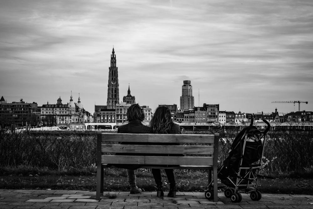 Straatfotografie in Antwerpen - Linkeroever. Dit jong verliefd koppel geniet van het uitzicht terwijl hun kind vredig slaapt in de buggy.