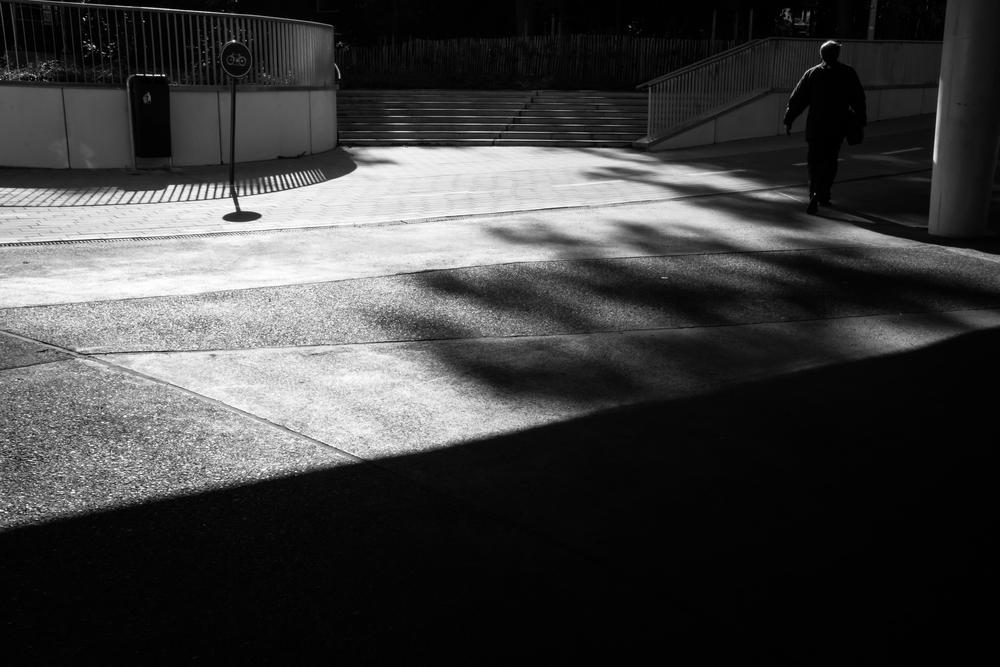 Ik volg deze man en hij neemt de juiste brug. Hij wandelt in de zon. Het strijklicht van de zon geeft een mooie schaduw.