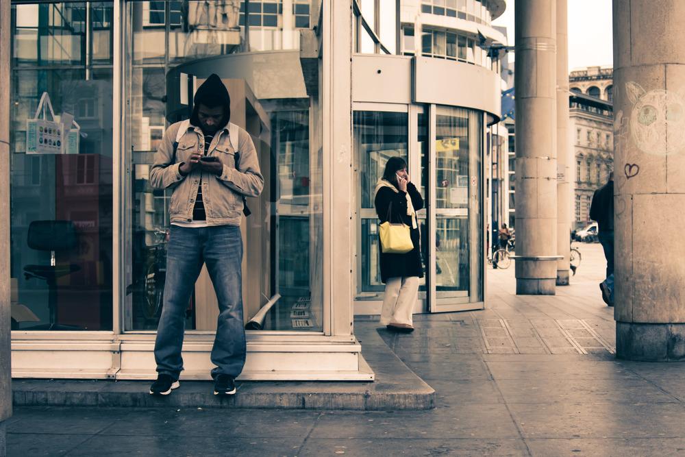 Aan de bibliotheek in Gent zie ik deze twee mensen bezig met hun smartphone. Thema straatfotografie.