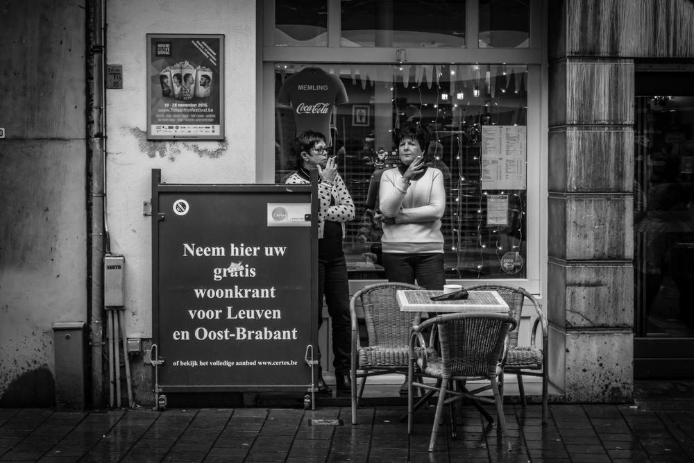 Straatfotografie in Leuven - 2 rokende dames discussiëren met elkaar over de kerstaankopen
