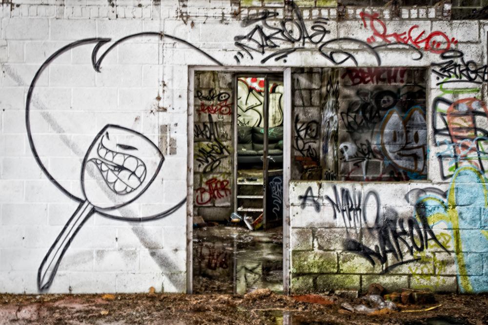 Urbex fotografie is niet zonder gevaar. Dit is een lege garage aan de kant van een drukke weg. Maar het is duidelijk dat ik niet de eerste bezoeker was.