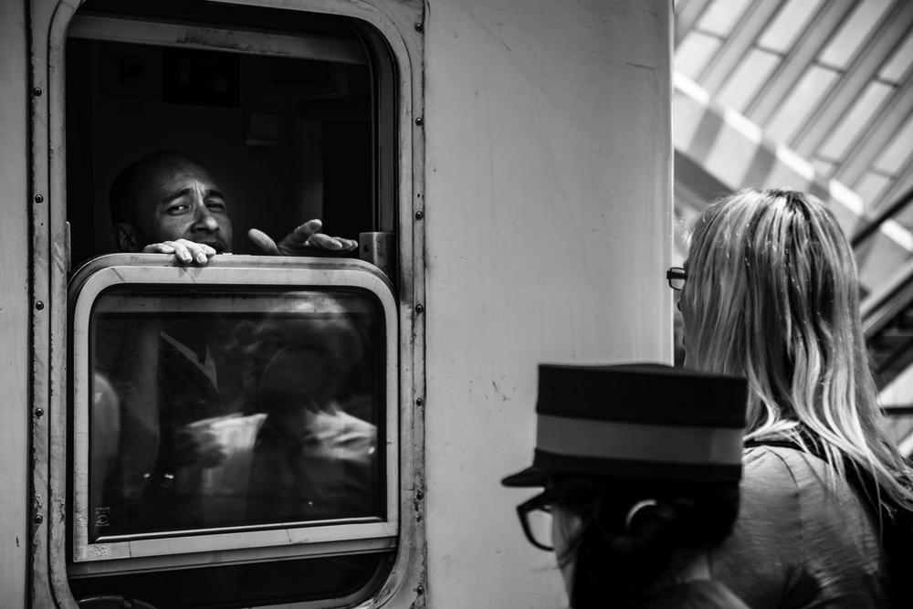 Viewfinder--straatfotografie-station-gare-guillemins-luik-mensen-man-kijkt-door-raam-treinwagon
