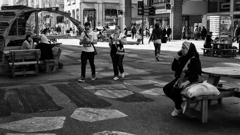 Viewfinder-straatfotografie-Brussel-eigenzinnige-fotografie-Anspachlaan-en-omgeving-allochtone-vrouw-telefoneert-met-smartphone