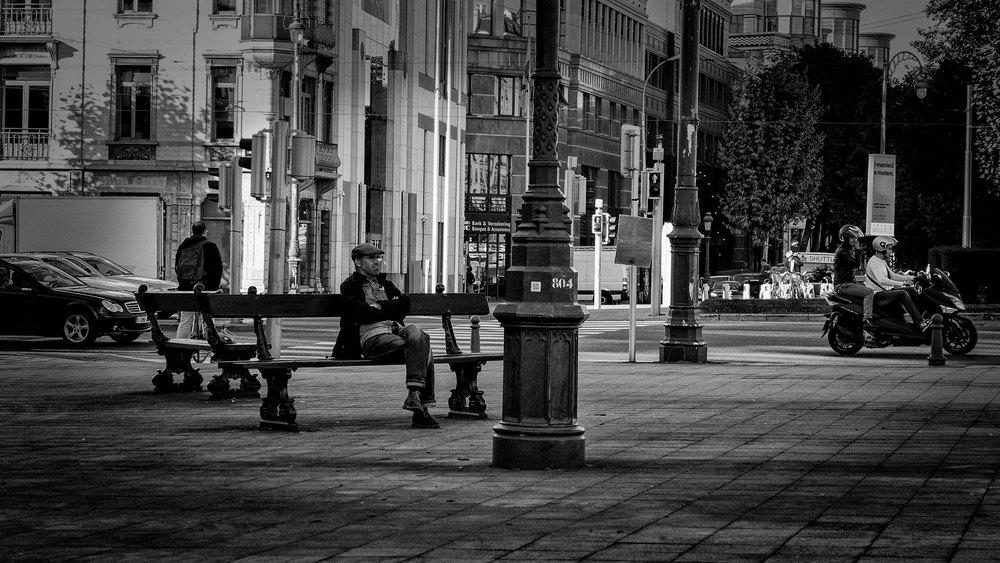 Viewfinder-straatfotografie-Brussel-eigenzinnige-fotografie-Anspachlaan-en-omgeving-man-wacht-en-kijkt-naar-verkeer-op-Brusselse-kleine-ring