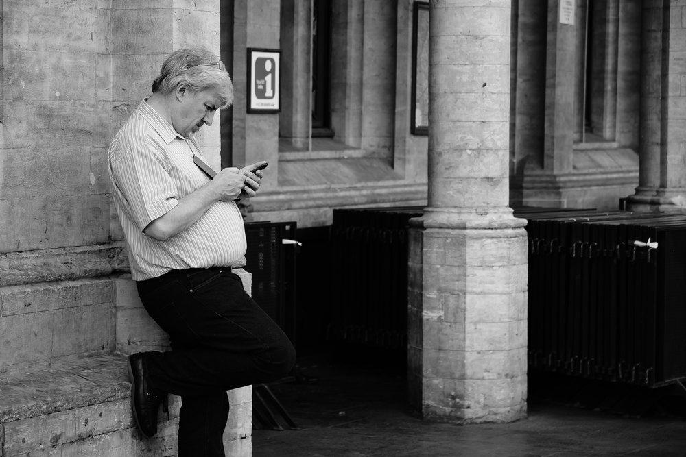 viewfinder-straatfotografie-brussel-man-checkt-email