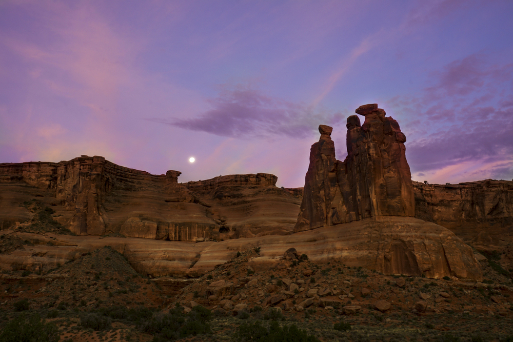 The moon beginning to set during sunrise at Sheep Rock