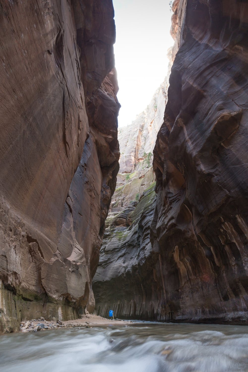 A hiker being dwarfed by the canyon walls