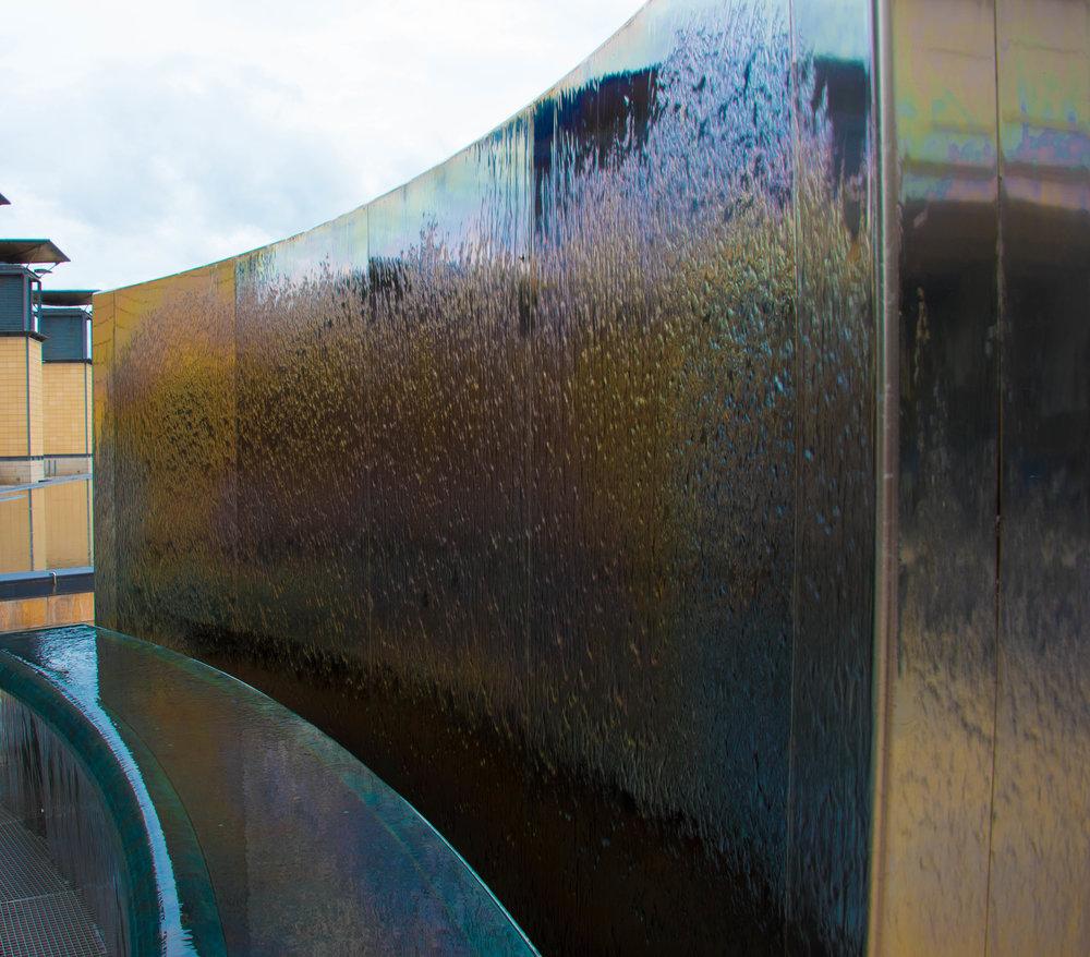 Moderne bykunst av stål og rennende vann