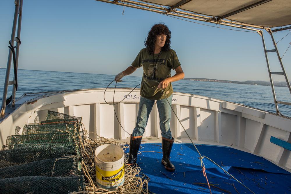 Irene all'alba, impegnata insieme al marito e al figlio nella pesca conle nasse. Capita sempre più spesso che di notte il pescato venga rubato da pescatori abusivi locali.