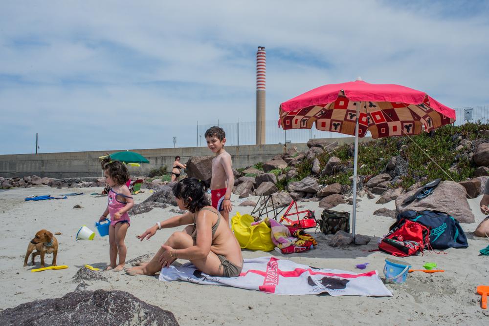 Una famiglia trascorre una domenica estiva in questa piccola spiaggia del porto industriale. In questa insenatura, a ridosso del bacino dei fanghi rossi, vige il divieto di balneazione e di pesca in seguito alla morte di sei persone risucchiate da una condotta industriale di scarico.
