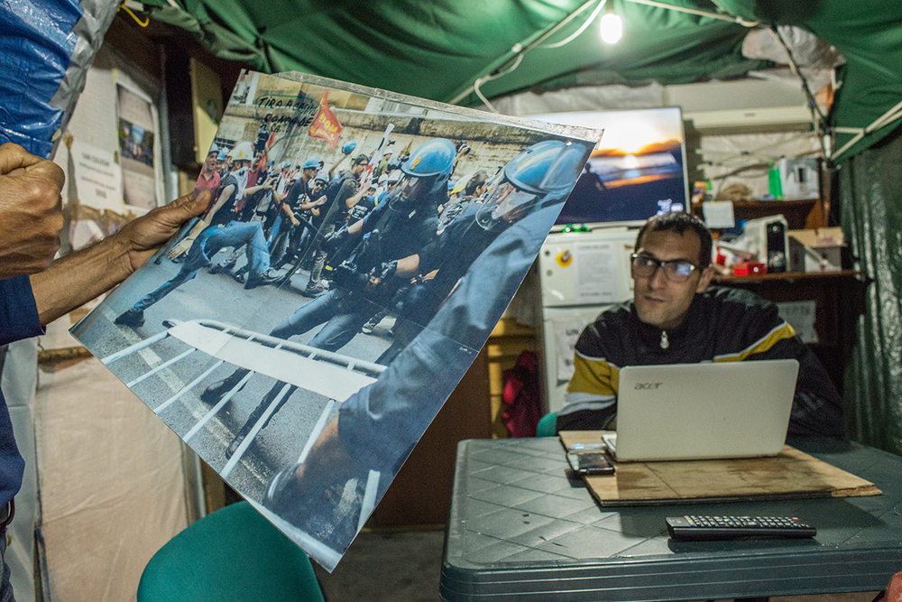 Lavoratori Alcoa, nella tenda centrale del presidio, ricordano gli scontri con la polizia durante una delle tante manifestazioni in seguito alla quale trentuno di loro hanno ottenuto il patteggiamento a un mese di reclusione con pena sospesa, per l'accusa di interruzione di pubblico servizio. Nel gennaio del 2010 avevano invaso la pista dell'aeroporto cagliaritano di Elmas bloccando lo scalo in un blitz estremo per impedire la chiusura degli impianti.
