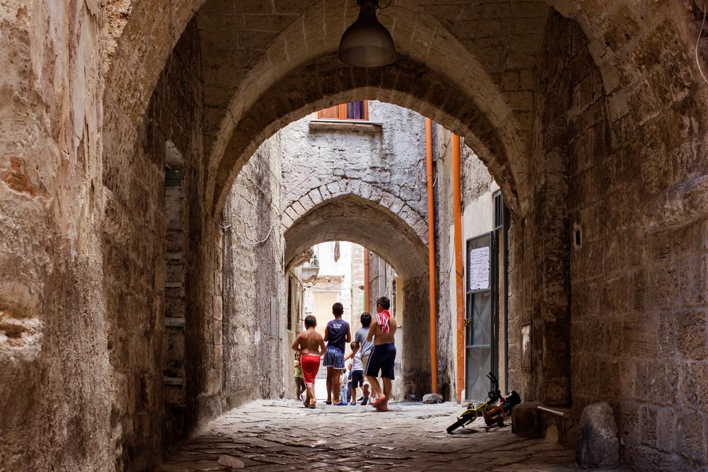 Taranto, Italia, 5 Agosto 2013. Nei vicoli della Città Vecchia di Taranto. Nel 2011, l'amministrazione tarantina aveva attivato la procedura per far riconoscere la Città Vecchia come Patrimonio dell'Umanità dall'UNESCO, ma venne rifiutata per la totale assenza di un piano di recupero. Gli unici lavori di restauro vengono effettuati per evitare crolli.