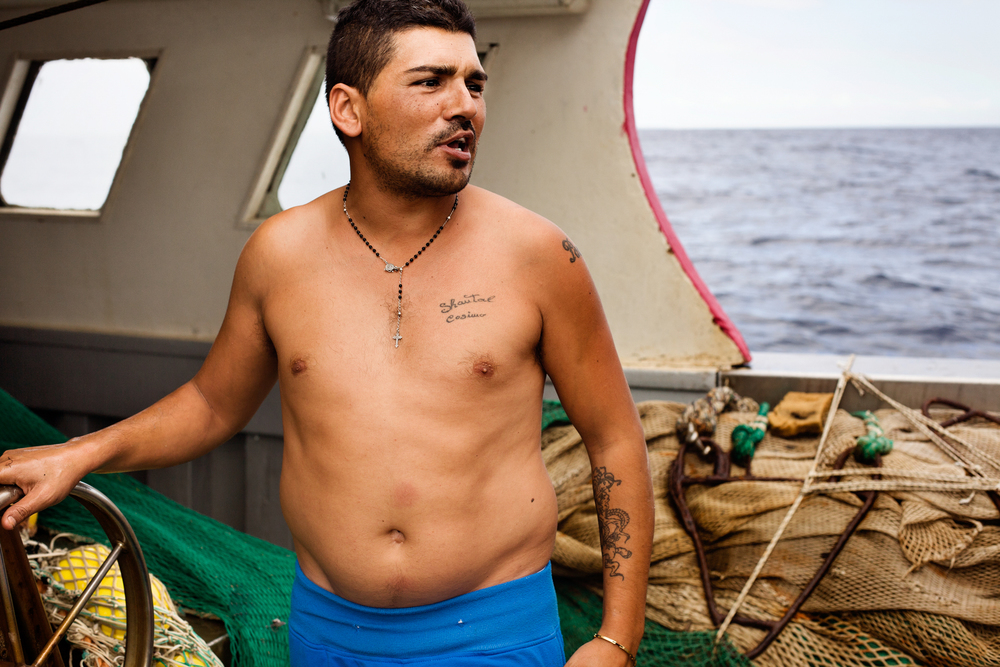 Taranto, Italia, 19 Settembre 2013. Antony, pescatore di Taranto, al comando della sua barca durante una battuta di pesca a strascico nel golfo di Taranto.