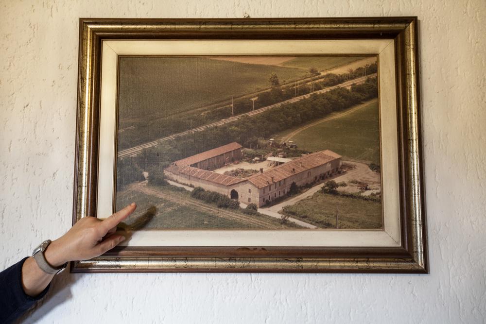 La moglie di un contadino mostra una vecchia foto aerea della propria cascina e dei campi circostanti.Brescia / Italia. Ottobre 2013