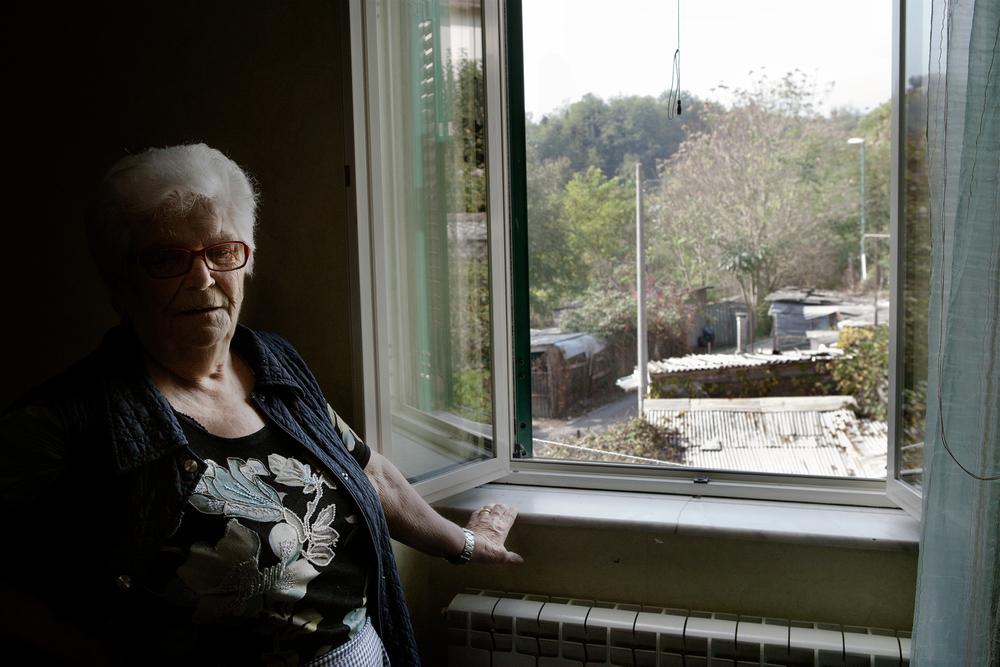 """Maria lamenta la presenza di un forte inquinamento nella sua città. Dalla finestra di casa sua vede i terreni delle Ferrovie dello Stato, dove sono state costruite rimesse agricole in eternit.Colleferro """"scalo"""", novembre 2013"""