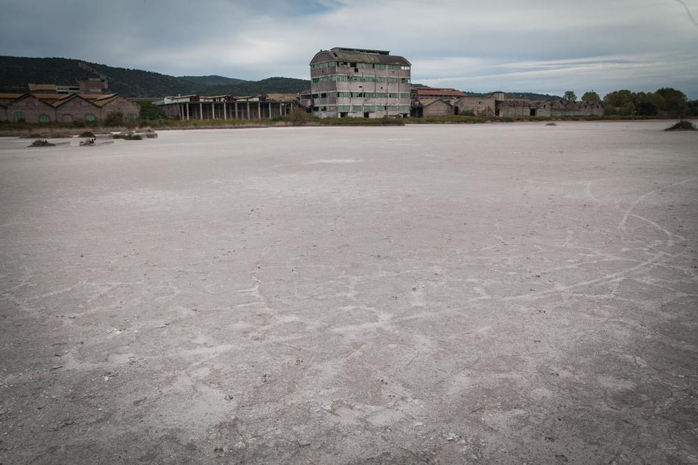 """""""Deserto bianco"""" di silice amorfa, S.I.To.Co. Orbetello (Grosseto), 2015.Dalla chiusura dello stabilimento nel 1993, i lavori di messa in sicurezza della fabbrica sono iniziati solo nel 2004. Nel bacino lagunare di fronte al """"deserto bianco"""" venne edificata una palizzata, mai terminata, per evitare che la silice amorfa sversasse in laguna. Oggi l'acqua del bacino attiguo è completamente bianca."""