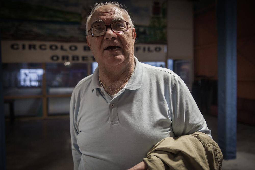 Paolo Ferrini, ex-dipendente della S.I.To.Co., nel Circolo Bocciofilo di Orbetello (Grosseto), 2015.Ha lavorato al concimificio per 28 anni. Si occupava del magazzino e faceva parte del consiglio di fabbrica. Il giorno dello stop alle macchine si trovava alla trattativa con gli industriali a Grosseto. Per difendere il posto di lavoro ci fu una mobilitazione dei dipendenti che rimasero per giorni a dormire negli uffici amministrativi dello stabilimento.