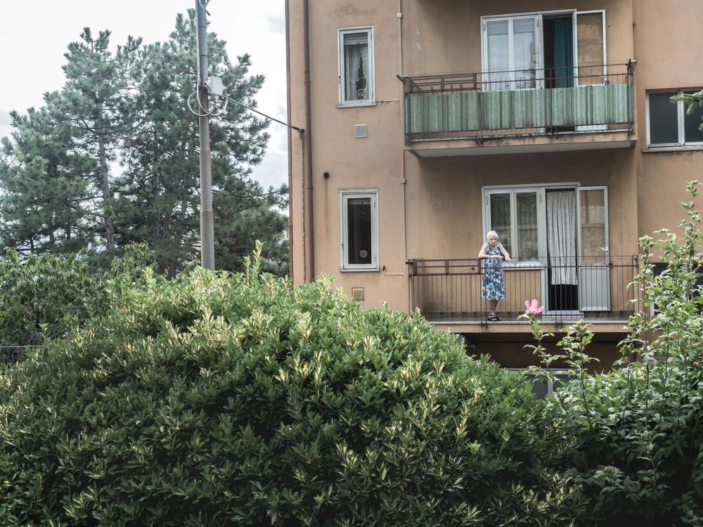 Un'anziana si affaccia dal suo appartamento nel rione di Servola, alle spalle della sua abitazione sorge l'impianto siderurgico, Trieste 2015.