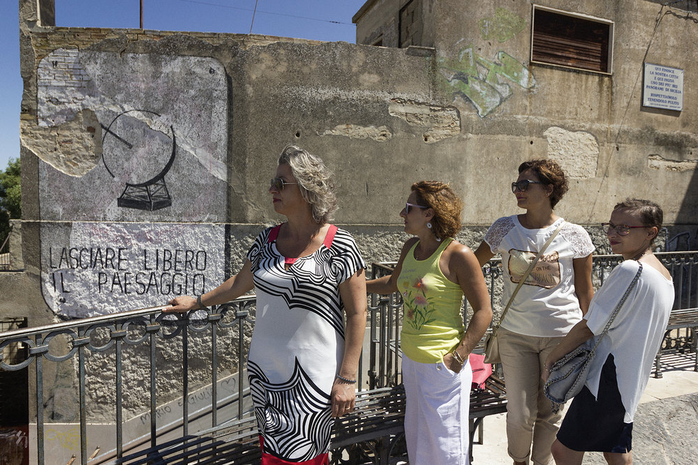 Niscemi (CL), Luglio 2017. Concetta Gualato, Luisa Cicero, Bonina Amato, Silvia Palermo; alle spalle uno dei tre murales di Blu. Nel 2013, durante la stagione più accesa delle proteste per contrastare la costruzione del MUOS, un consistente gruppo di donne del Comitato Mamme No MUOS (700 iscritte) metteva in atto una serie di blocchi stradali, impedendo l'accesso alla base sia ai militari americani, sia agli operai che si recavano al cantiere per le operazioni di edificazione delle parabole. © Chiara Faggionato