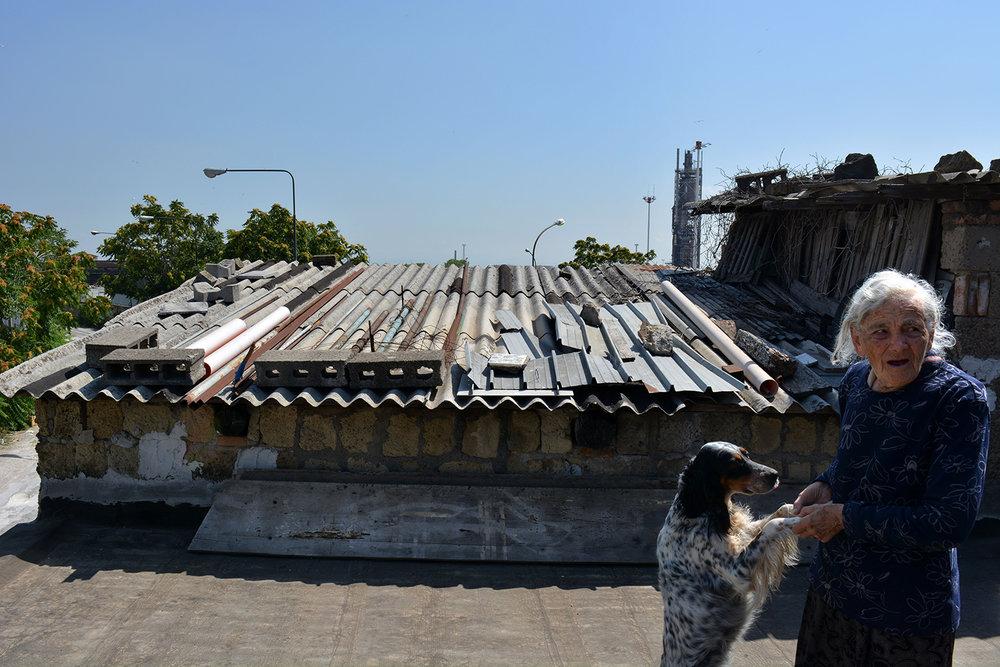 San Giovanni a Teduccio (Napoli), 2017. Anna Improta la cui abitazione è davanti al deposito Agip. Alle sue spalle il vecchio inceneritore e una discarica.© Alice Tinozzi