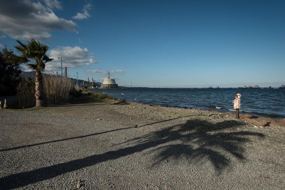 Sul lato sud dell'insediamento industriale una strada di campagna conduce al Porto Foxi. Un terzo dello specchio d'acqua di Sarroch è interdetto alla navigazione. Sarroch (Cagliari), 2017.