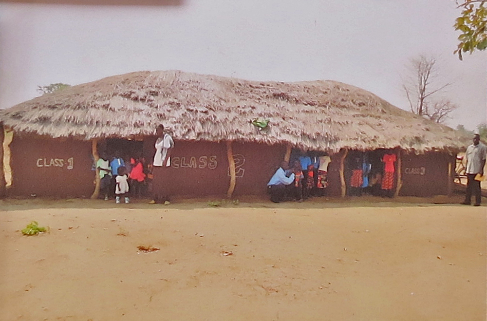 Three temporary classrooms - grass roofs, mud walls, pole supports