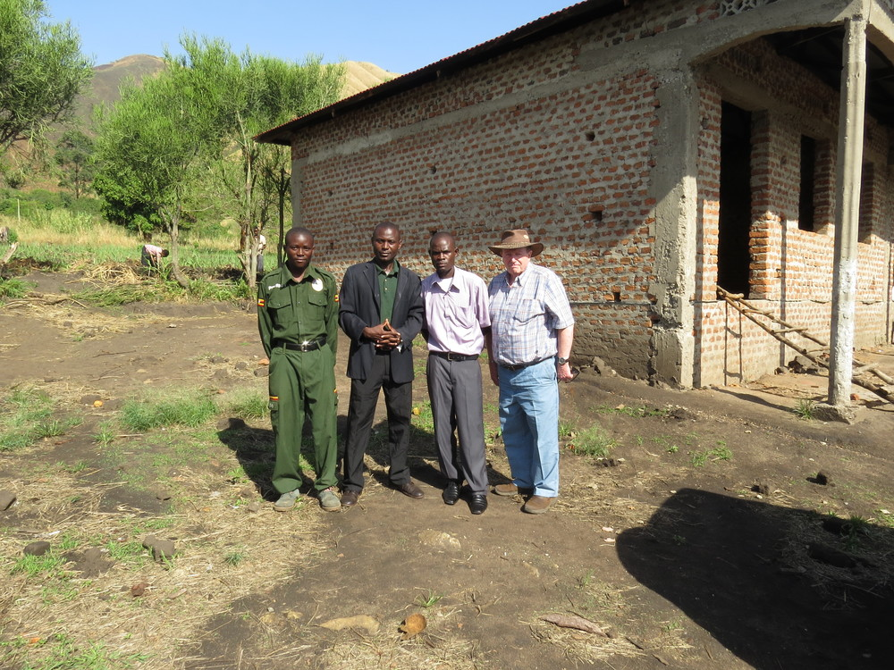 School leaders and Classrooms for Africa representative outside first permanent building