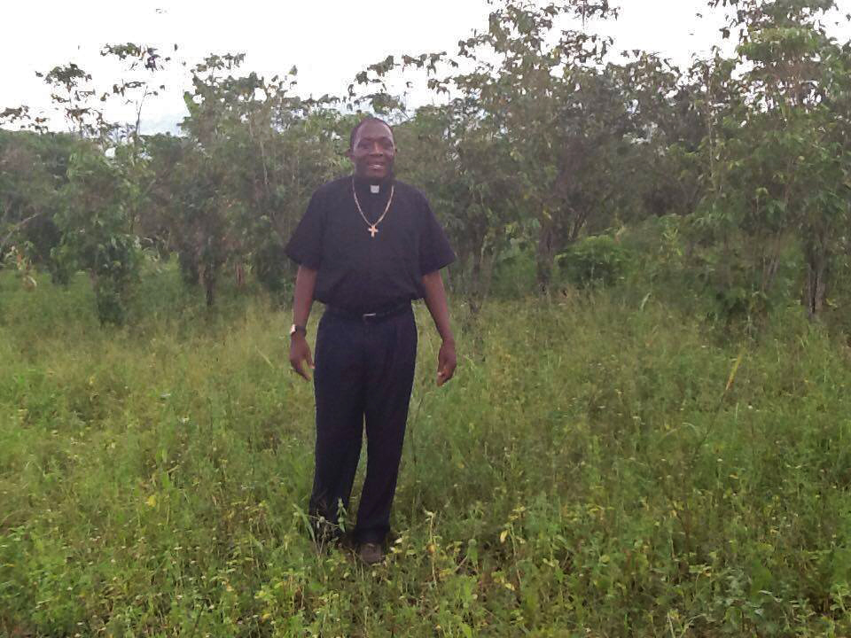 Bishop Tom standing in the newly acquired piece of land from the community to construct the primary section.jpg