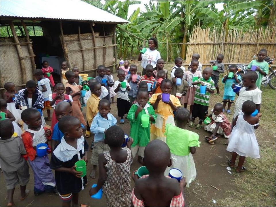 Children at New Covenant having a cup of porridge at 10am.jpg