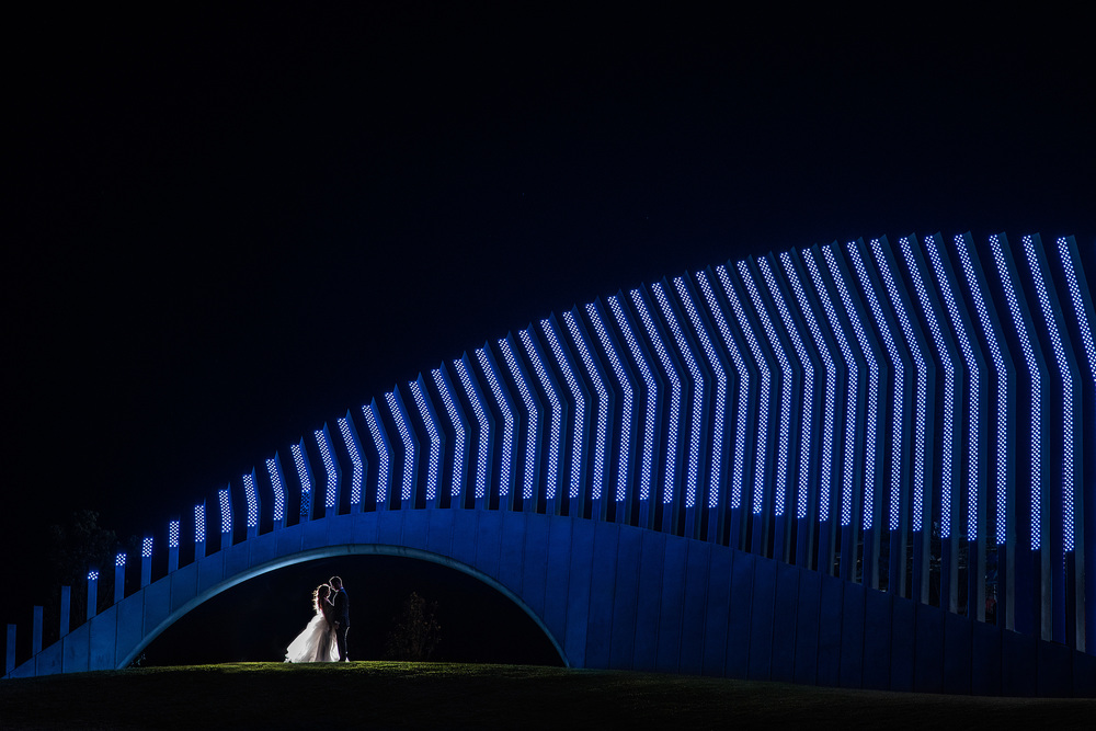 bride and groom portrait under a light structure in ottawa ontario
