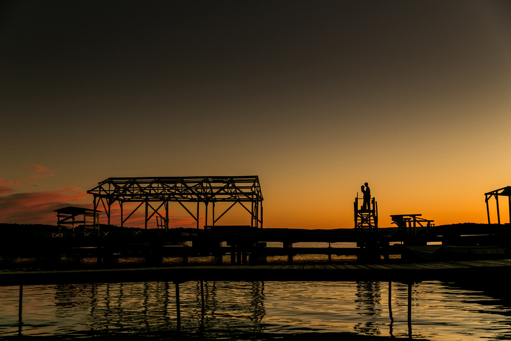 Bride and groom silhouette portrait during sunset on a lakeside dock