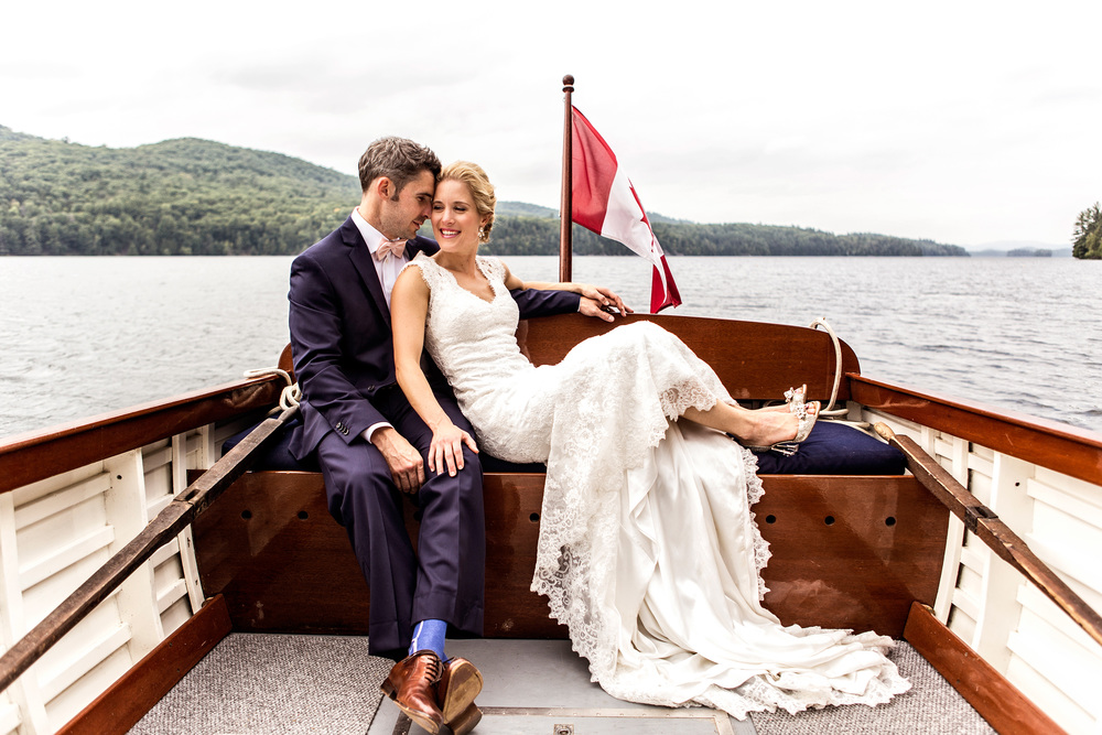 Bride and groom in a boat taking a tour around the lake after their cottage wedding