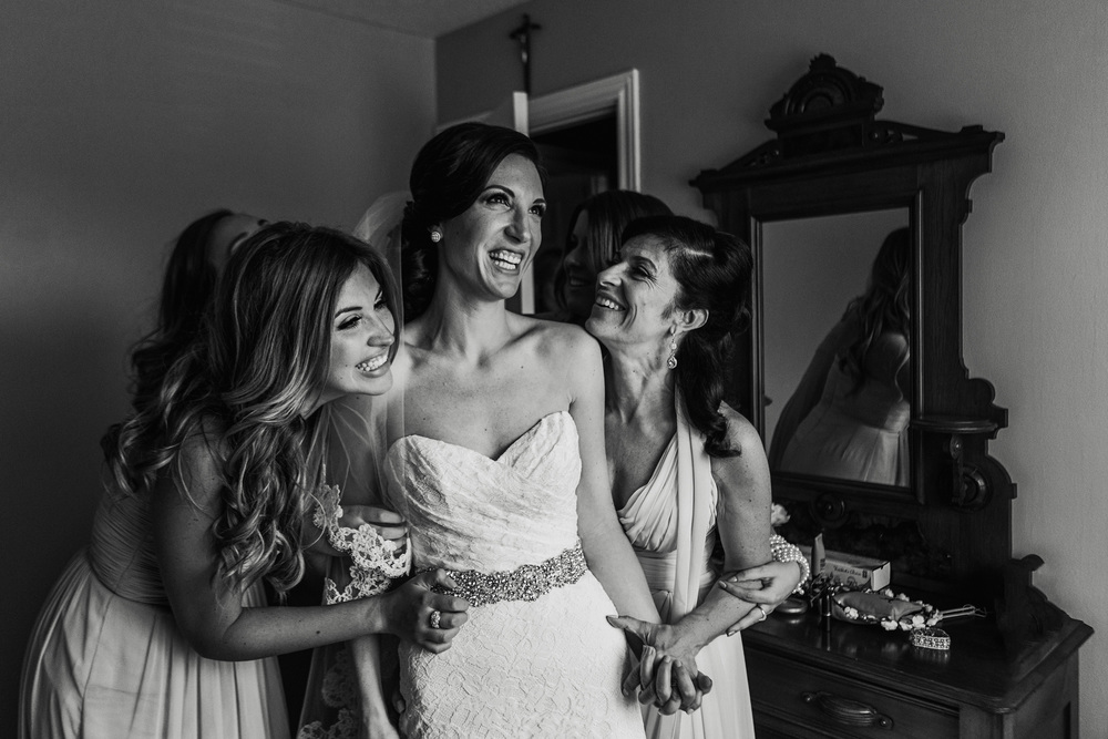 Mother of bride and bridesmaids hug bride after putting her wedding dress on