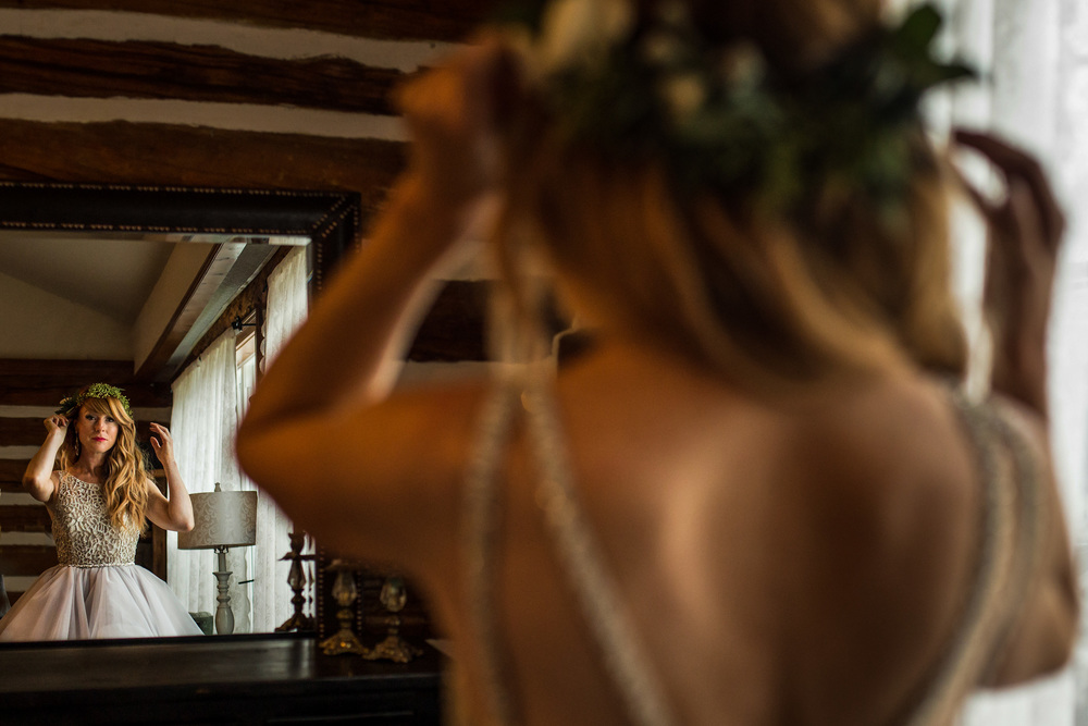 bride making final adjustments in mirror before heading to wedding ceremony at a stonefields wedding