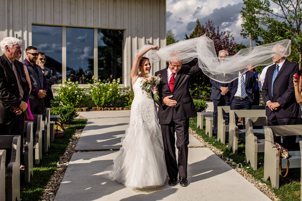brides veil takes flight while walking down aisle with father during a le belvedere wedding