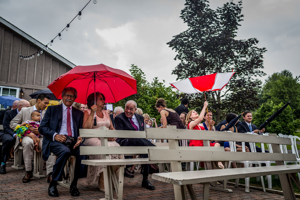 wedding guest has trouble with umbrella during a rainy wedding at strathmere