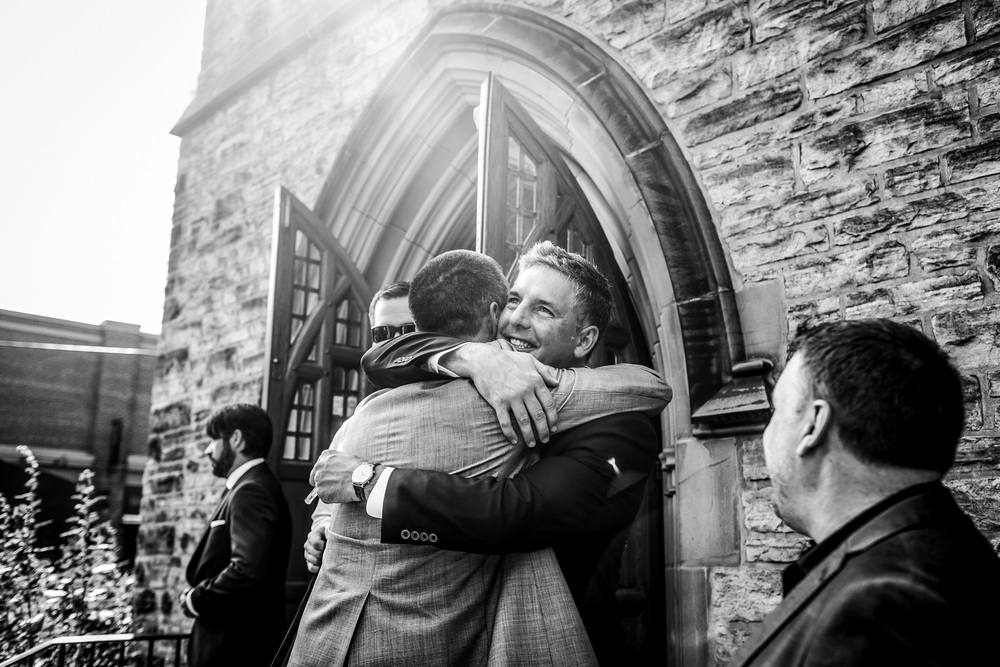 groom hugs brother after knox church wedding in ottawa