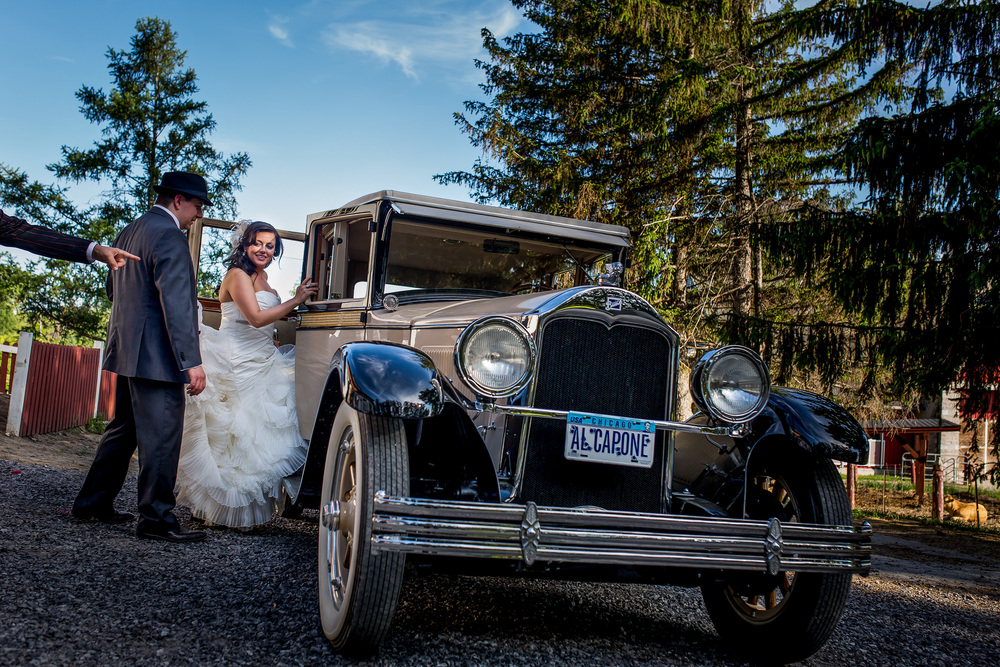 bride and groom getting into capone vintage car