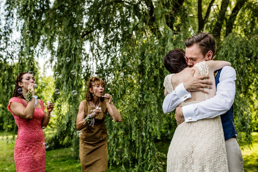 groom hugs bride during a wedding ceremony at experimental farm ottawa
