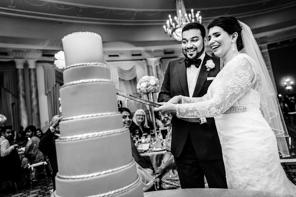 bride and groom cut cake during a chateau laurier wedding reception in the adam room