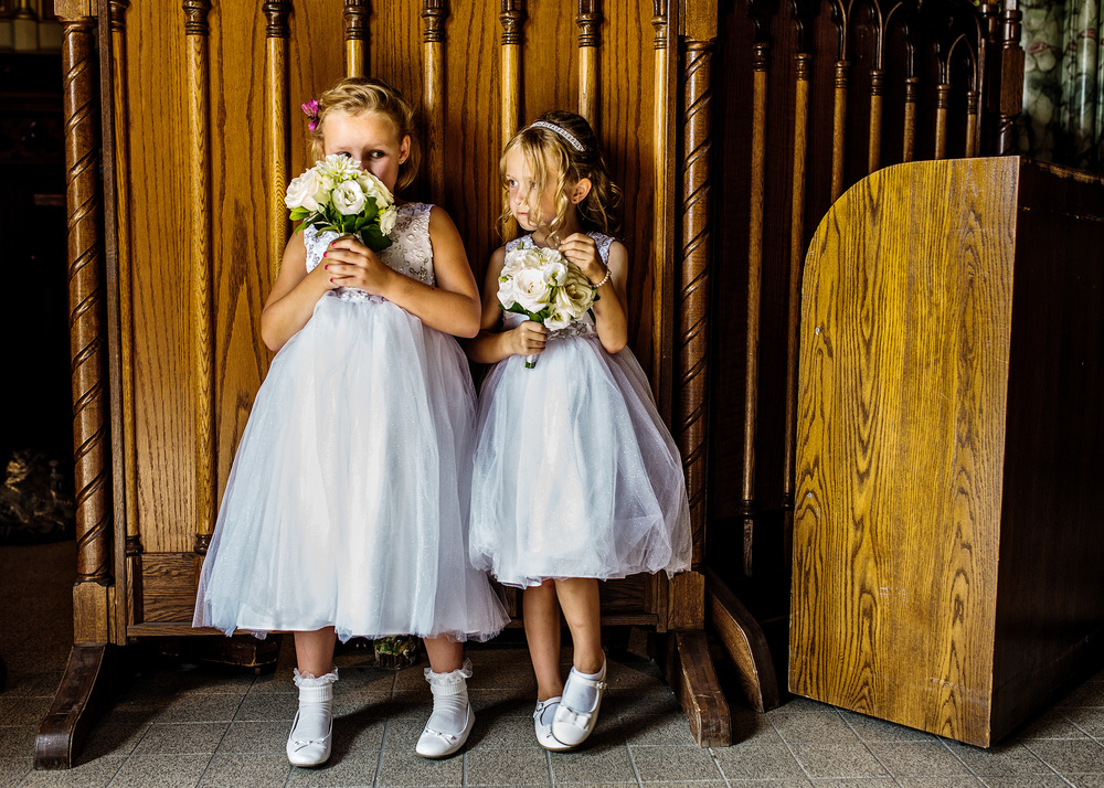 flower girls smelling flowers before a notre dame bascillica wedding in ottawa