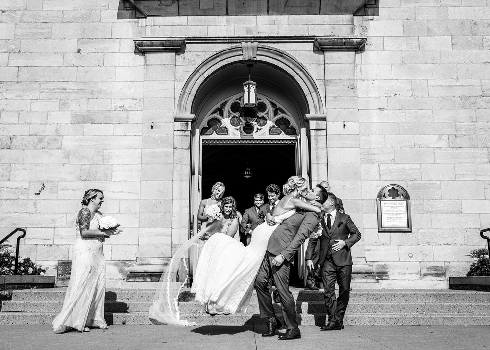 groom lifts bride after a notre dame bascillica wedding in ottawa
