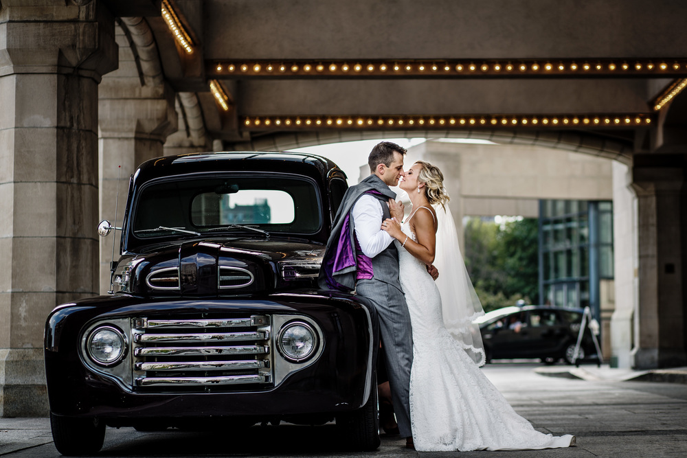 bride and groom pose against a vintage truck outside the fairmont chateau laurier before wedding ceremony