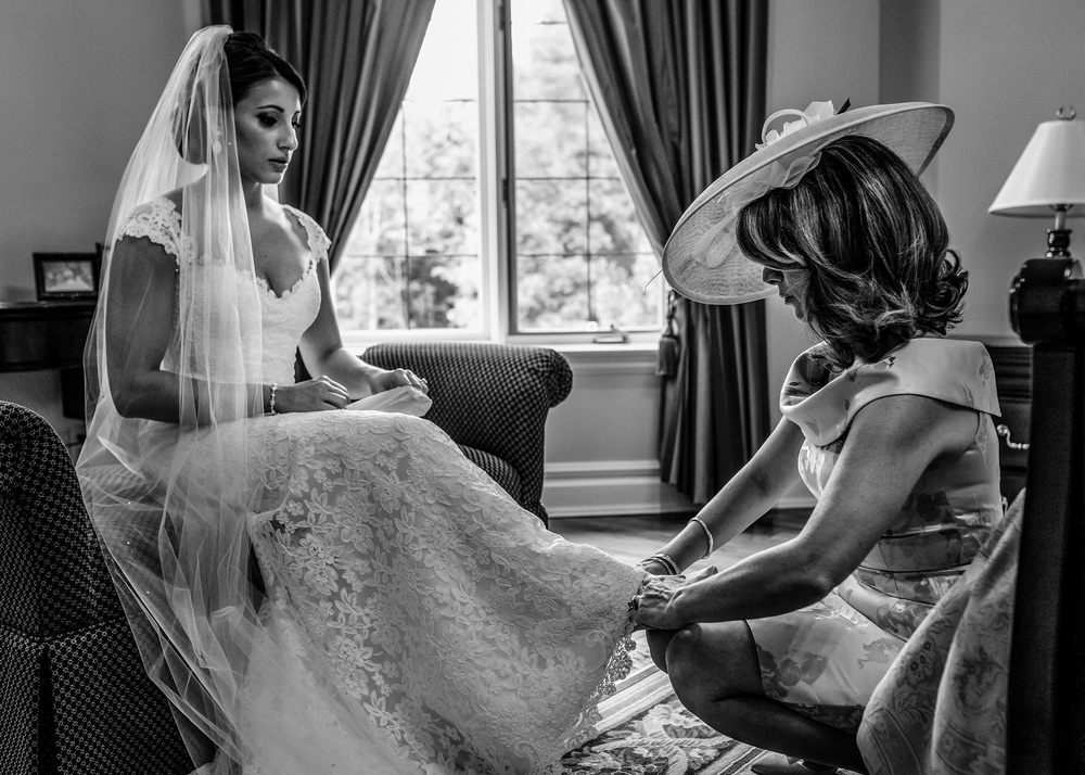 brides mother helps bride with shoes before a le belvedere wedding in wakefield quebec